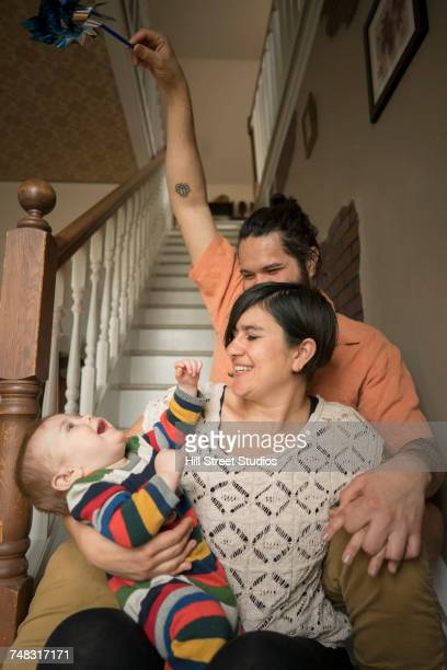 Mother and father sitting on staircase playing with baby boy