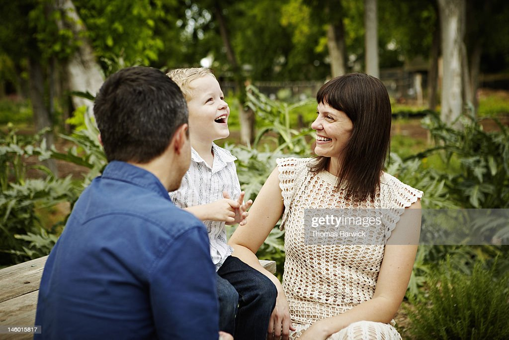 Mother and father sitting with son smiling : Bildbanksbilder