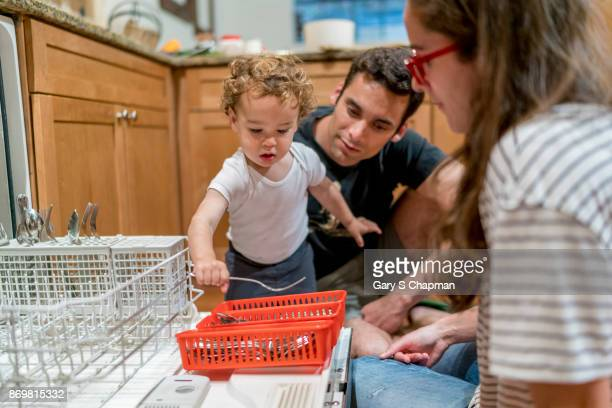 Mother and father teach their toddler boy to put away clean dishes.
