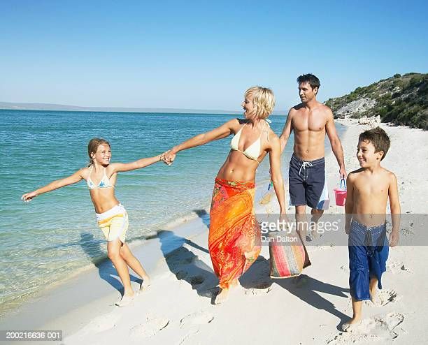 Mother and father walking on beach with son and daughter (7-9)