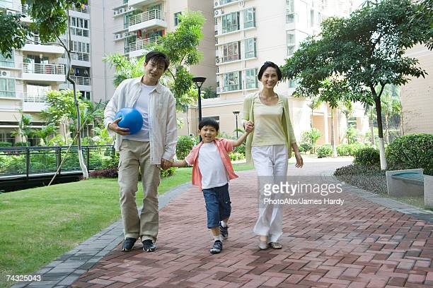 mother and father walking with son, holding hands - femme entre deux hommes photos et images de collection