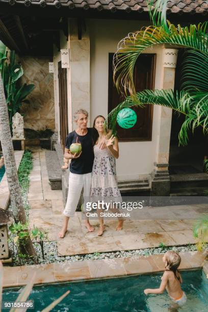 mother and father watching daughters  swimming in swimming pool - expatriate stock pictures, royalty-free photos & images