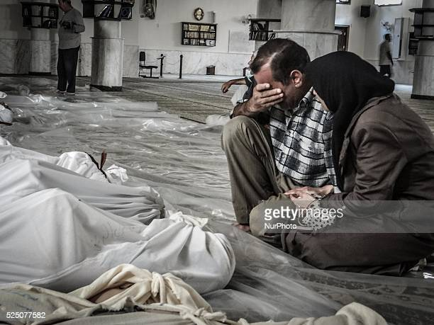 A mother and father weep over their child's body who was killed in a suspected chemical weapons attack on the Damascus suburb of Ghouta in August 21...
