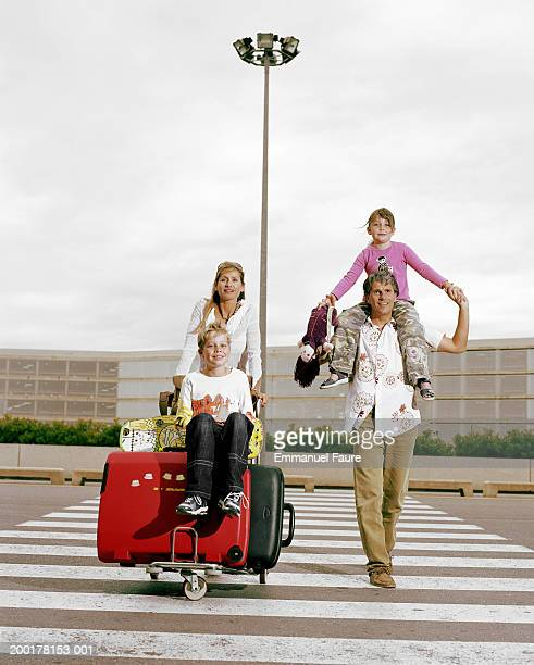 Mother and father with children (6-10) crossing street of airport