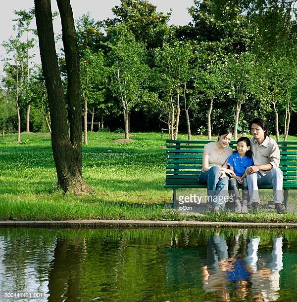mother and father with daughter sitting on bench near lake - china oriental - fotografias e filmes do acervo