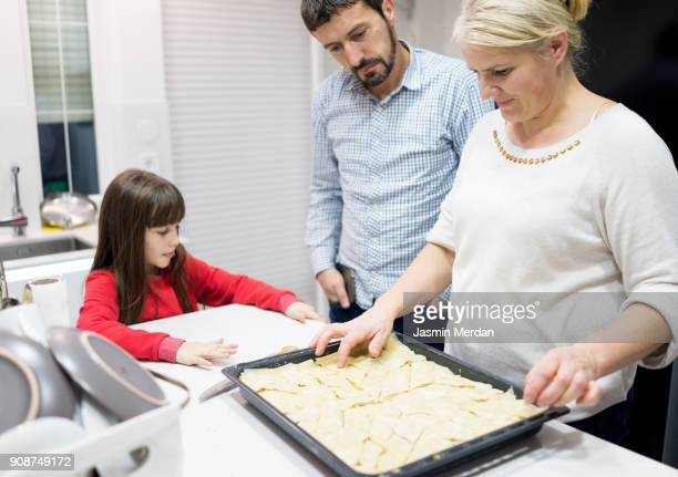 Mother and father with kid in kitchen making sweet