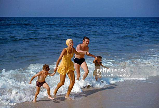 A mother and father with son and daughter running out of the ocean Palm Beach Florida 1947