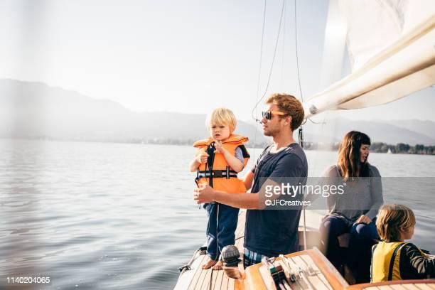 mother and father with sons on sailboat - wasserfahrzeug stock-fotos und bilder