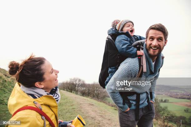 a mother and father with their son on the fathers back, whilst walking in the countryside - family with one child stock pictures, royalty-free photos & images