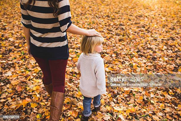Mother and female toddler walking through autumn leaves