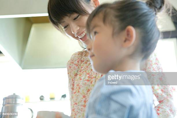 Mother and girl cooking together