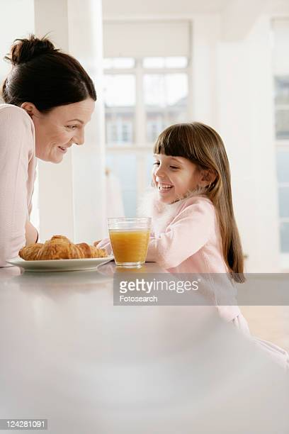 Mother and girl having breakfast at kitchen counter
