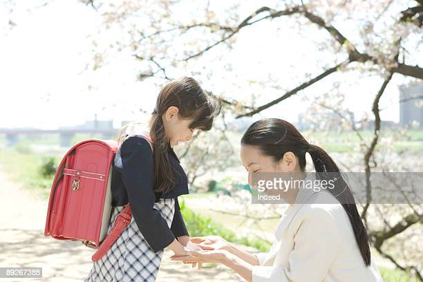 mother and girl (8-9) holding hands, looking down - satchel bag stock photos and pictures