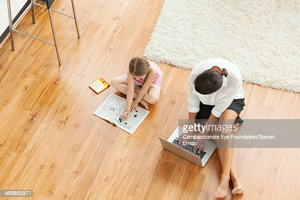 Mother and girl (6-7) on floor in living room