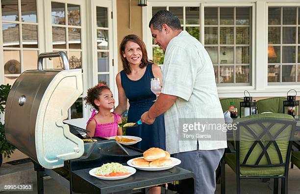 Mother and girl on patio holding plate being served barbeque food by father