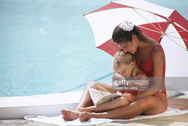 Mother and girl (6-7) poolside reading book