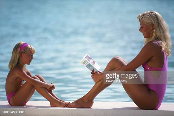 Mother and girl (4-5) sitting by poolside, mother reading book