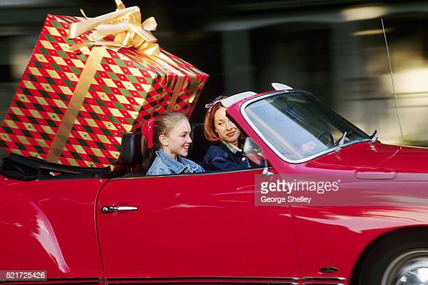 Mother and girl with huge gift in back of convertible