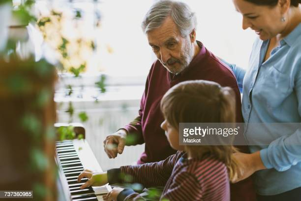 Mother and great grandfather looking at boy playing piano in house