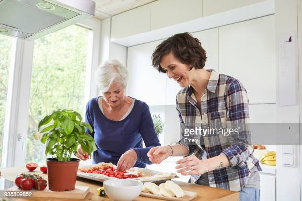 Mother and grown daughter at home, preparing food together