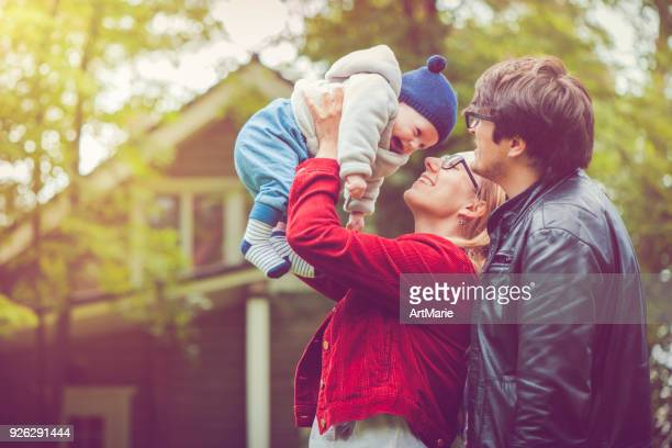 mother and her baby boy near house - young family stock pictures, royalty-free photos & images