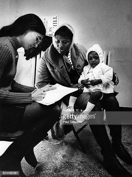 A mother and her baby daughter are seen by medical personnel at a Black Panther community health clinic in a south side neighborhood Chicago Illinois...