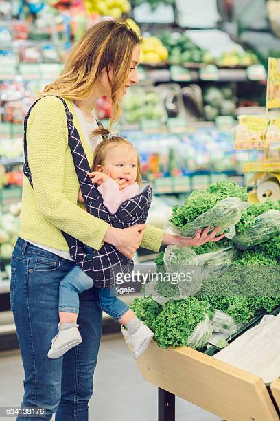 Mother And Her Baby Daughter Buying Vegetable In Local Supermarket.