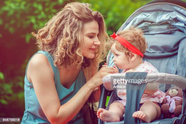 mother and her baby daughter in stroller in park - pushchair stock pictures, royalty-free photos & images