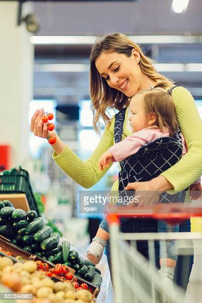 Mutter und Baby Tochter Gemüse einkaufen.