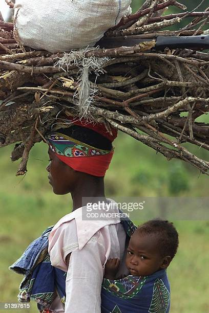 A mother and her baby return to the displaced people's camp in the village of Chiaquelane some 180 km north of Maputo after collecting firewood for...