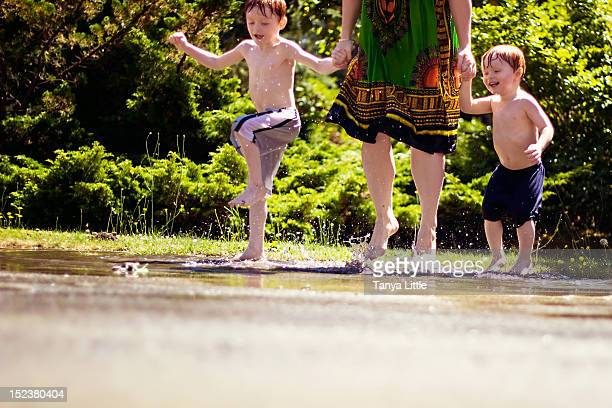 Mother and her boys jumping in puddle
