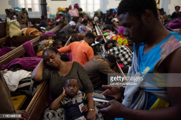A mother and her child are seen sitting in the Methodist Church after a scuffle broke out earlier in the day in Cape Town on November 15 2019 A...