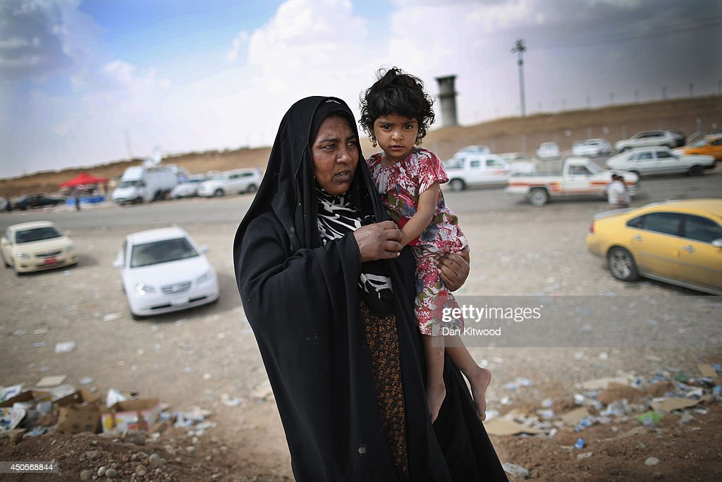 A mother and her child arrive at a Kurdish checkpoint on June 13, 2014 in Kalak, Iraq. Thousands of people have fled Iraq's second city of Mosul after it was overrun by ISIS (Islamic State of Iraq and Syria) militants. Many have been temporarily housed at various IDP (internally displaced persons) camps around the region including the area close to Erbil, as they hope to enter the safety of the nearby Kurdish region.