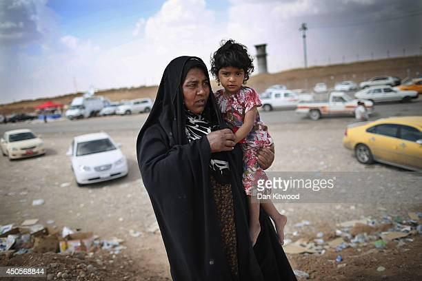 Mother and her child arrive at a Kurdish checkpoint on June 13, 2014 in Kalak, Iraq. Thousands of people have fled Iraq's second city of Mosul after...