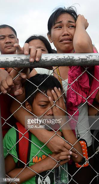 Mother and her child cry as they beg authorities for seats on flights by military C-130 planes out at the airport in Tacloban, Leyte province,...