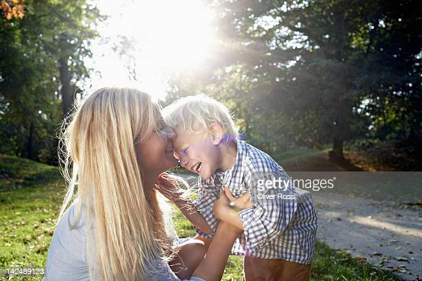 mother and her child cuddling in a park - mother stock-fotos und bilder