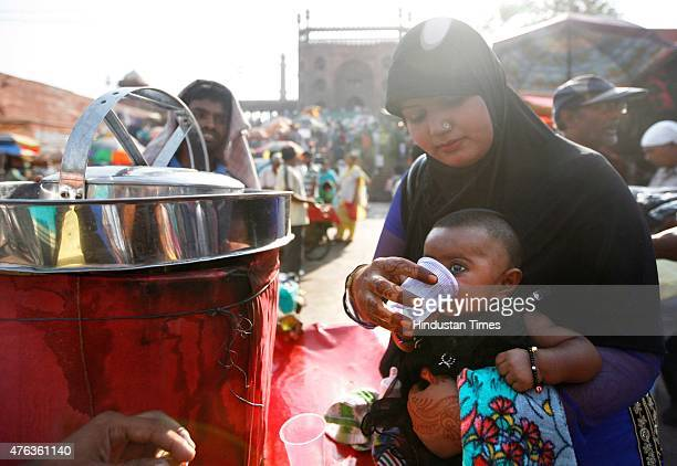 A mother and her child drinking water during a hot weather in front of Jama Masjid as heat wave conditions prevailed in Northern India as the mercury...