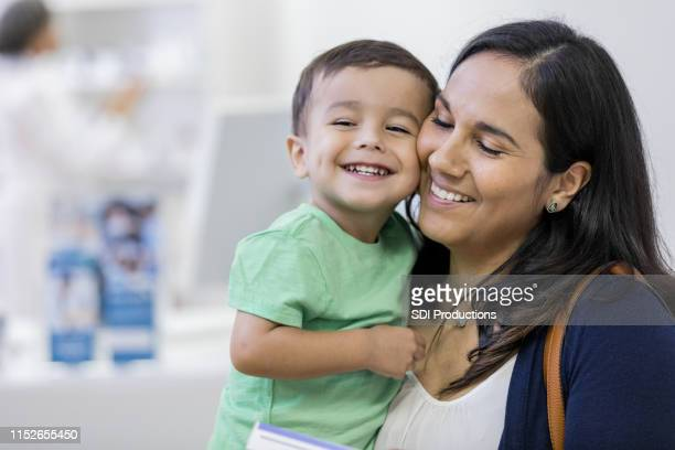 a mother and her child embrace lovingly at store - toddler stock pictures, royalty-free photos & images