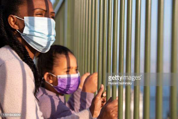 mother and her child in face masks looking away through the fence bars. coronavirus pandemic concept. - child behind bars stock pictures, royalty-free photos & images