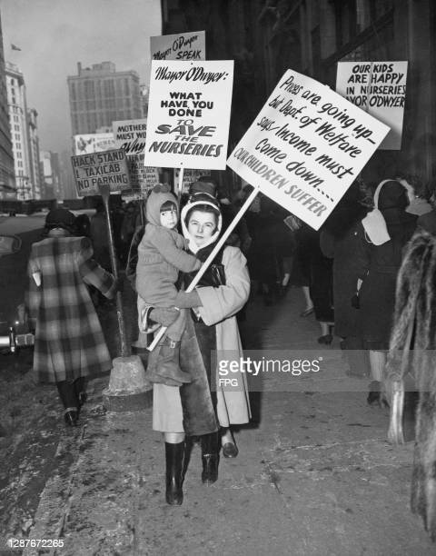 Mother and her child join protestors carrying placards reading 'Mayor O'Dwyer What Have You Done to Save the Nurseries' and 'Prices Are Going Up But...