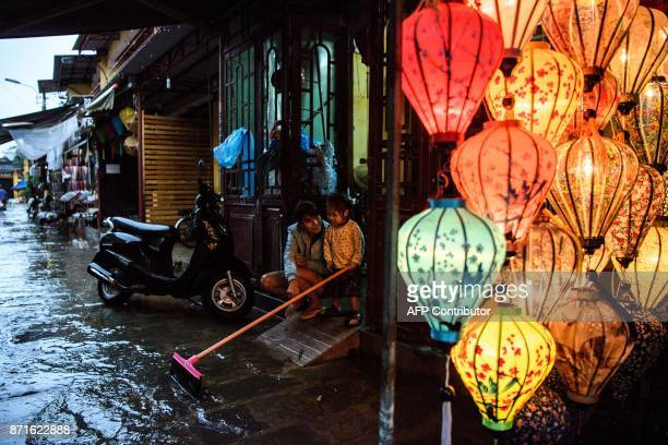 TOPSHOT A mother and her child sit in their house entrance next to a lantern shop in the town of Hoi An on November 8 2017 following days of heavy...