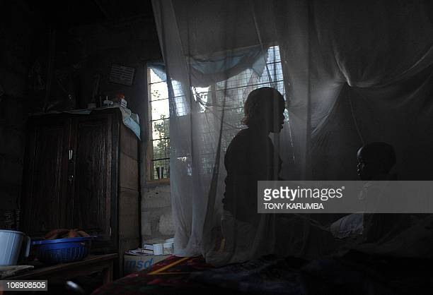 A mother and her child sit on October 30 2009 on a bed covered with a mosquito net near Bagamoyo 70 kms north of Tanzanian capital Dar es Salaam...
