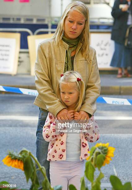 A mother and her child stand in front of the department store where Swedish Foreign Minister Anna Lindh was stabbed on September 13 2003 in Stockholm...