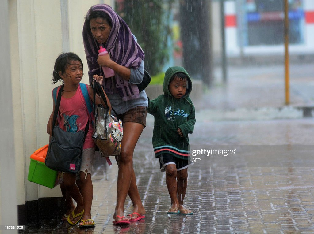 A mother and her children brave heavy rains as they head for an evacuation center amidst strong winds as Typhoon Haiyan pounded Cebu City, in central Philippines on November 8, 2013. One of the most intense typhoons on record whipped the Philippines on November 8, killing three people and terrifying millions as monster winds tore roofs off buildings and giant waves washed away flimsy homes.