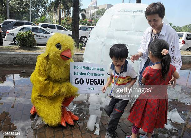 A mother and her children look at a member of People for the Ethical Treatment of Animals wearing a chicken costume while holding a placard which...