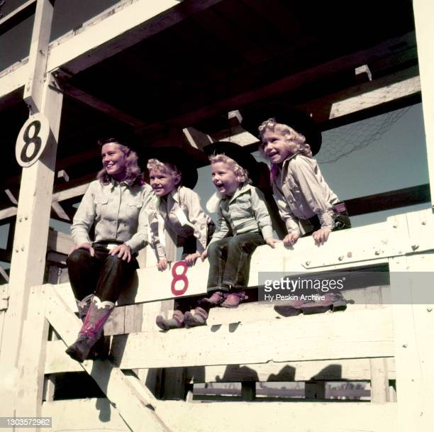 Mother and her children sit on a railing during a day at the rodeo circa 1950.