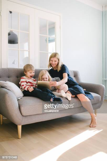 mother and her children using digital tablet in the living room - scandinavian home stock pictures, royalty-free photos & images