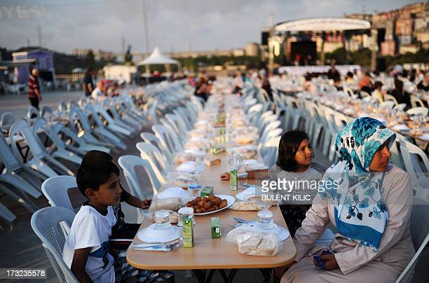A mother and her children wait for breaking their fasting on July 10 2013 at Eyup in Istanbul Tens of millions across the Muslim world fast from dawn...