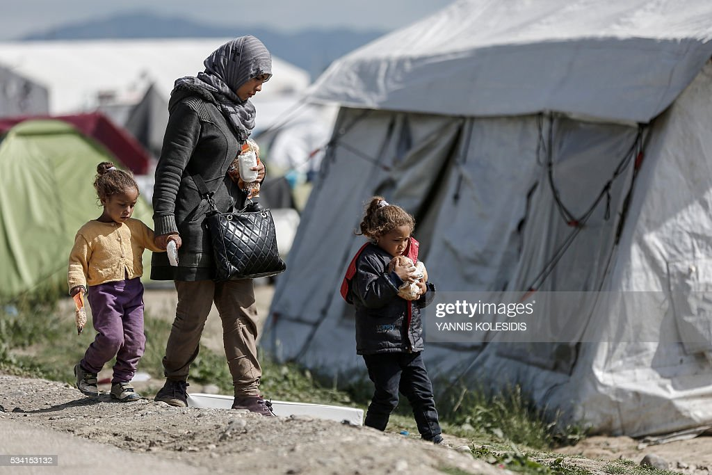 A mother and her children walk past tents during a police operation to clear a makeshift c& for refugees and migrants at the border between Greece and ... & A mother and her children walk past tents during a police ...