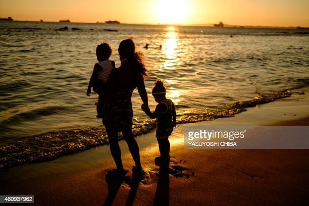 A mother and her children watch the sunset at Boa Viagem beach in Salvador Brazil on December 31 2014 AFP PHOTO / YASUYOSHI CHIBA